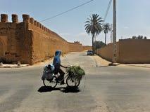 Bemannen Sie das Fahren Fahrrads auf die afrikanische Straße lizenzfreie stockbilder