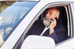 Bemannen Sie das Fahren seines Autos und die Unterhaltung am Telefon Lizenzfreie Stockfotografie