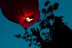 Bemannen Sie das Freigeben einer chinesischen Laterne im Himmel Stockbilder