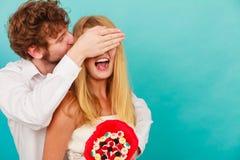 Bemannen Sie das Geben des Frauensüßigkeitsbündels, das ihre Augen bedeckt Stockbild