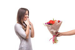 Bemannen Sie das Geben eines Blumenstraußes und überraschte Frau lokalisiert Stockfotografie