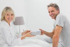 Bemannen Sie das Geben seinem lächelnden Partner vorhanden, der Kamera betrachtet Lizenzfreie Stockbilder