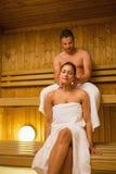 Bemannen Sie das Geben seiner Freundin einer Halsmassage in der Sauna Stockbild