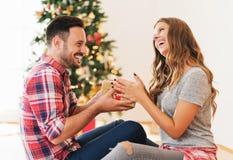 Bemannen Sie das Geben seiner Freundin eines Weihnachtsgeschenks Lizenzfreie Stockfotos