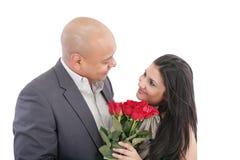 Bemannen Sie das Geben seiner hübschen Freundin eines Blumenstraußes der roten Rosen lizenzfreie stockfotos