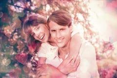 Bemannen Sie das Geben seiner hübschen Freundin eines Doppelpol im Park, der an der Kamera lächelt Lizenzfreies Stockbild