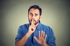 Bemannen Sie das Geben von Shhhh-Ruhe, Ruhe, geheime Geste auf grauem Wandhintergrund Stockbilder