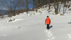 Bemannen Sie das Gehen durch den Schnee, der ein Skikostüm trägt stock video footage