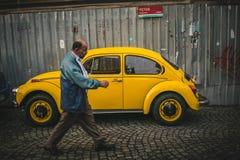 bemannen Sie das Gehen durch gelbes Weinlese Volkswagen-kafer nahe Zaun Lizenzfreie Stockbilder