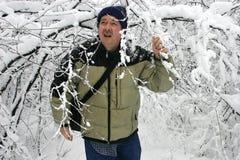 Bemannen Sie das Gehen durch Schnee gefüllte Zweige 2 Lizenzfreies Stockfoto