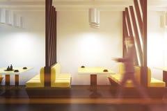 Bemannen Sie das Gehen in einen gelben Sofarestaurantinnenraum Stockbilder