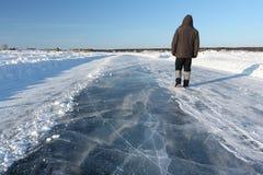 Bemannen Sie das Gehen entlang eine Straße des Eises auf dem gefrorenen Reservoir Stockbild