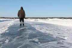 Bemannen Sie das Gehen entlang eine Straße des Eises auf dem gefrorenen Reservoir Lizenzfreies Stockfoto