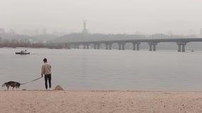 Bemannen Sie das Gehen mit seinem Hund auf dem Strand in stock video footage