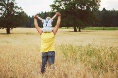 Bemannen Sie das Gehen mit seinem Kind auf dem Gebiet Lizenzfreie Stockfotografie