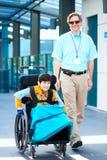 Bemannen Sie das Gehen nahe bei kleinem Jungen im Rollstuhl außerhalb des medizinischen fac Stockbild