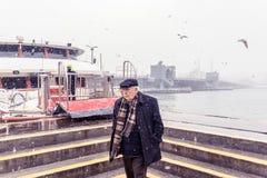 Bemannen Sie das Gehen nahe Pier Karakoy Uskudar an einem schneebedeckten Tag im Winter Lizenzfreie Stockbilder