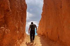 Bemannen Sie das Gehen in Richtung zum Himmel in einem Durchgang des roten/orange Felsens stockfotos