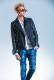 Bemannen Sie das Gehen und die Aufstellung beim Tragen von Jeans und von Lederjacke Lizenzfreie Stockbilder