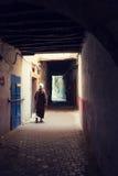 Bemannen Sie das Gehen unten in eine beschattete Gasse im Medina von Essaouira, Stockfotografie