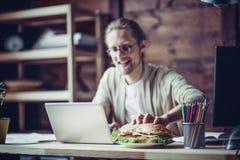 Bemannen Sie das Gehen zu Hause bearbeiten, am Arbeitsplatz zu essen Lizenzfreies Stockfoto