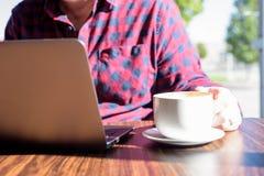 Bemannen Sie das Genießen eines Latte beim Woking auf einer Laptop-Computer Lizenzfreies Stockbild