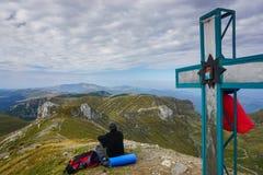 Bemannen Sie das Genießen der Ansicht über eine Spitze, die durch ein Kreuz in den Bergen markiert wird Stockfoto