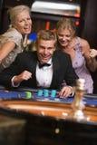 Bemannen Sie das Gewinnen am Roulettetisch, der durch glamor umgeben wird Stockfoto