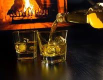 Bemannen Sie das Gießen von zwei Gläsern Whisky mit Eiswürfeln vor dem Kamin Lizenzfreie Stockfotografie
