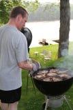 Bemannen Sie das Grillen von Steaks für 4. des Juli-Feiertagspicknicks Stockbild