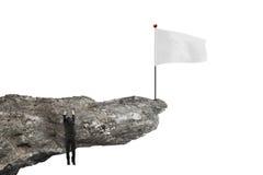 Bemannen Sie das Hängen an der Klippe mit leerer Flagge und Weiß Stockbilder