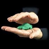 Bemannen Sie das Höhlen seiner Hände um ein grünes eco Auto Lizenzfreies Stockbild