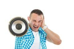 Bemannen Sie das Hören laute Musik, die Sprecher hält und Ohren bedeckt Lizenzfreie Stockfotografie