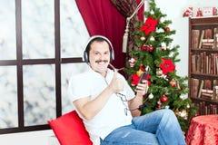 Bemannen Sie das Hören Musik auf Kopfhörern nahe einem Weihnachtsbaum Stockfotos