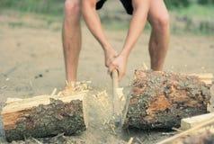 Bemannen Sie das Hacken des Brennholzes mit einer Axt auf einem sandigen Strand in der Bewegung lizenzfreies stockbild