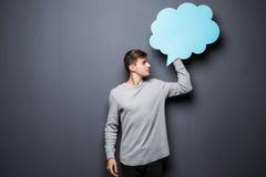 Bemannen Sie das Halten der blauen leeren Spracheblase mit Raum für Text auf grauem Hintergrund Stockfotografie