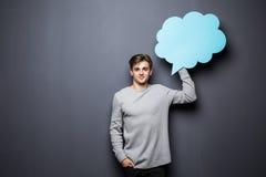 Bemannen Sie das Halten der blauen leeren Spracheblase mit Raum für Text auf grauem Hintergrund Lizenzfreies Stockfoto