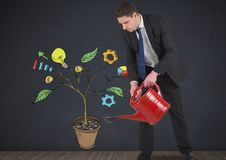Bemannen Sie das Halten der Gießkanne und das Zeichnen von kommerziellen Grafiken auf Betriebsniederlassungen auf Wand Stockfoto
