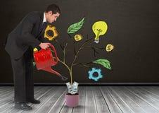 Bemannen Sie das Halten der Gießkanne und das Zeichnen von kommerziellen Grafiken auf Betriebsniederlassungen auf Wand Stockfotos