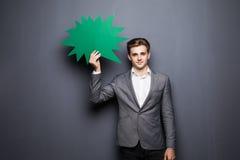 Bemannen Sie das Halten der grünen leeren Spracheblase mit Raum für Text auf grauem Hintergrund Stockbild