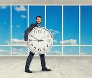 Bemannen Sie das Halten der großen Uhr und das Betrachten der Kamera Lizenzfreie Stockfotografie
