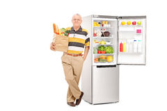 Bemannen Sie das Halten der Tasche mit Lebensmittelgeschäften durch einen offenen Kühlschrank Lizenzfreie Stockfotografie