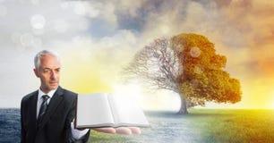Bemannen Sie das Halten des Buches mit magischer surrealer Saisonbaumphantasie stockfotos