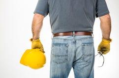 Bemannen Sie das Halten des gelben Sturzhelms beim Tragen von Arbeitshandschuhen Stockfotos