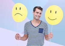 Bemannen Sie das Halten des glücklichen und traurigen Gesichtes gegen blauen Hintergrund Lizenzfreie Stockbilder