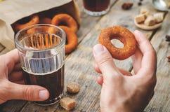 Bemannen Sie das Halten des Glases des Kaffee- und Kürbisdonuts Stockbild