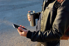 Bemannen Sie das Halten des Handys und der Thermo Schale, Reisebecher Lizenzfreies Stockbild