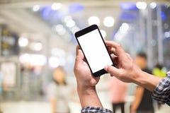 Bemannen Sie das Halten des intelligenten Telefons mit unscharfem Flughafenabfertigungsgebäudehintergrund Stockfotografie