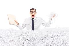 Bemannen Sie das Halten des Ordners in einem Stapel des zerrissenen Papiers Lizenzfreies Stockfoto