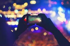 Bemannen Sie das Halten des Telefons und das Notieren eines Konzerts, das Machen von Fotos und das Genießen der Musikfestivalpart Stockfoto